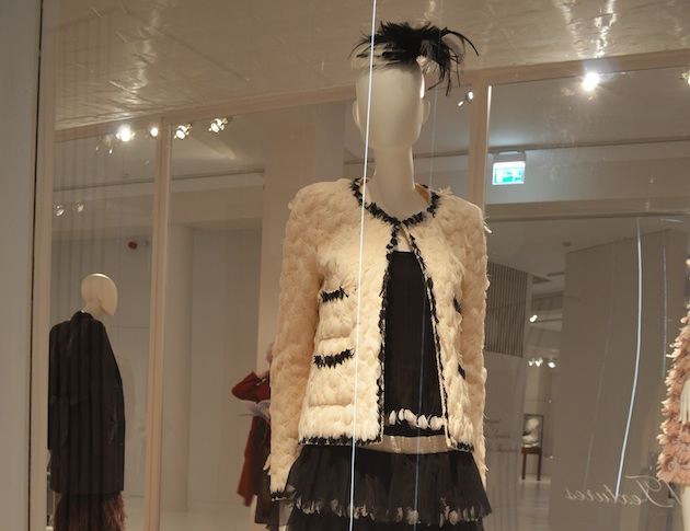Chanel, Haute Couture A/W 2004-2005. Ensemble consisting of a tweed vest with feathers embroidered in a braid, a long strapless dress with fine mousse line shoulder traps and a sur-jupe in silk pleaded mousse line decorated with ruche feathers. Comma-formed cap with feathers and a mousse line flower. Photo: Monica Ho