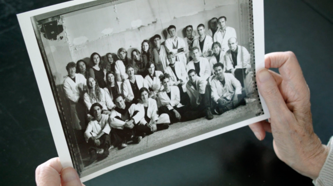 film still We Margiela documentary, hands Meirens holding photo group portrait Margiela team